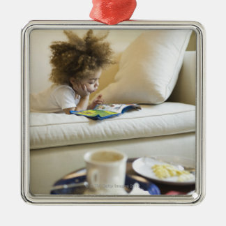 Mixed race boy reading book on sofa Silver-Colored square decoration