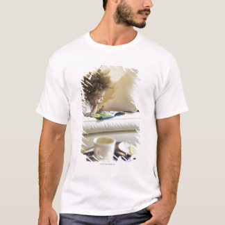 Mixed race boy reading book on sofa T-Shirt
