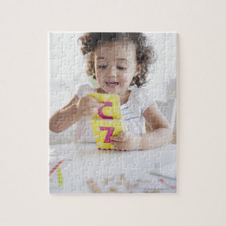 Mixed race girl playing with alphabet cards jigsaw puzzle