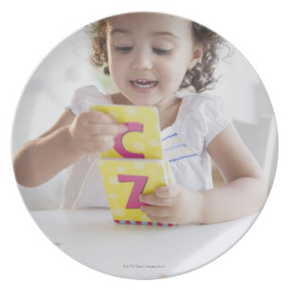Mixed race girl playing with alphabet cards plate