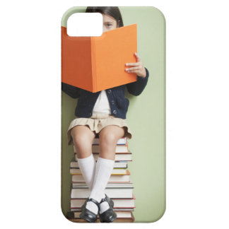 Mixed race girl sitting on stack of books iPhone 5 case