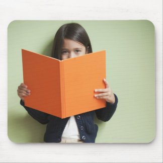 Mixed race girl sitting on stack of books mouse pad