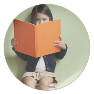 Mixed race girl sitting on stack of books plate