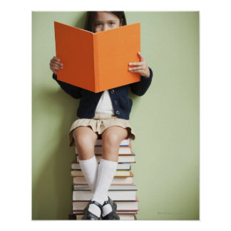 Mixed race girl sitting on stack of books poster