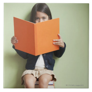 Mixed race girl sitting on stack of books tile