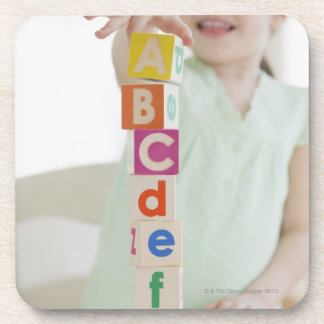 Mixed race girl stacking alphabet blocks beverage coasters