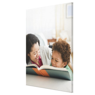 Mixed race mother reading book to son canvas print