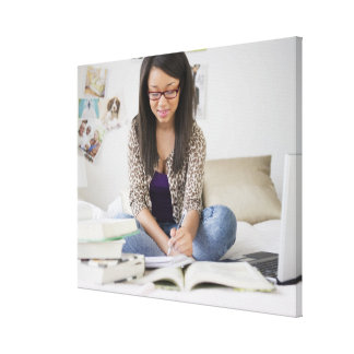 Mixed race teenage girl doing homework on bed canvas print