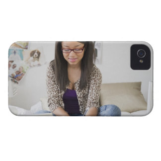 Mixed race teenage girl doing homework on bed iPhone 4 Case-Mate cases