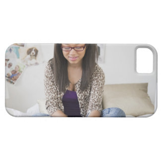 Mixed race teenage girl doing homework on bed iPhone 5 case