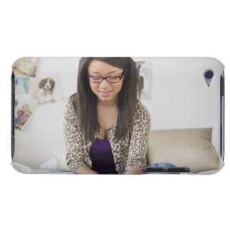 Mixed race teenage girl doing homework on bed iPod touch cover