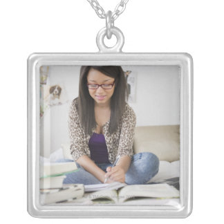 Mixed race teenage girl doing homework on bed necklace