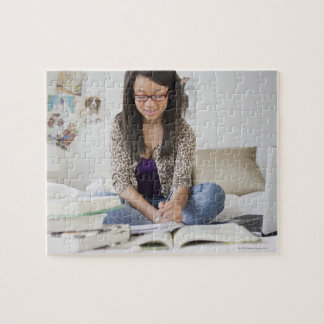 Mixed race teenage girl doing homework on bed puzzle