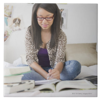 Mixed race teenage girl doing homework on bed tile