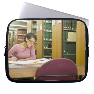 Mixed race woman doing research in library laptop sleeve