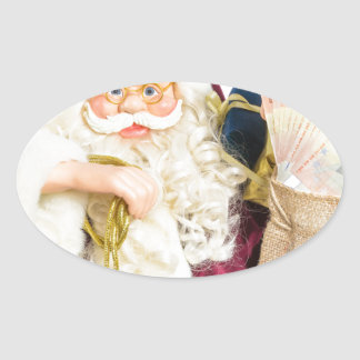 Model of Santa Claus with bell gifts and money Oval Sticker