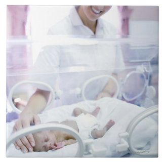MODEL RELEASED. Nurse and premature baby. Large Square Tile