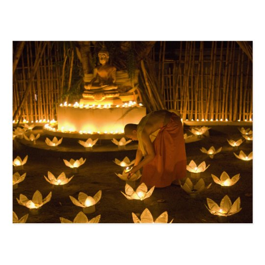 Monks lighting khom loy candles and lanterns for