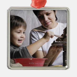 mother and daughter forming sculpture out of christmas ornament