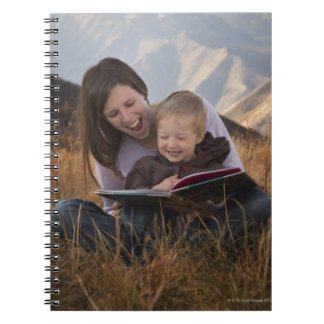 Mother and son reading outdoors notebook