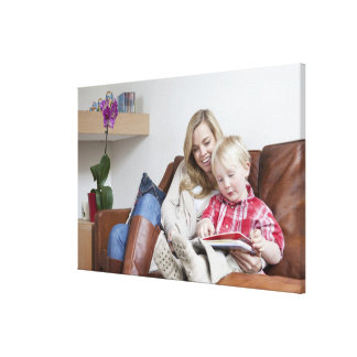 Mother and son sitting on sofa together canvas print