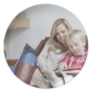 Mother and son sitting on sofa together plate