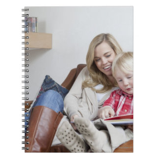 Mother and son sitting on sofa together spiral notebook