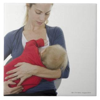 Mother breastfeeding her baby. tile