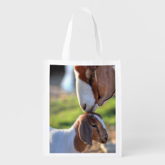 Mother goat kissing her baby on head. reusable grocery bag