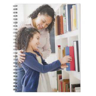 Mother helping daughter choose book on shelf