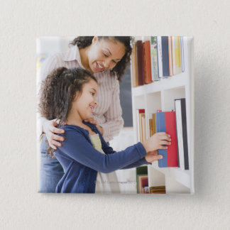 Mother helping daughter choose book on shelf 15 cm square badge