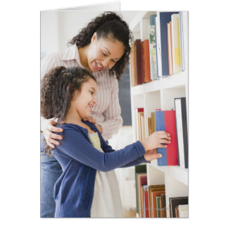 Mother helping daughter choose book on shelf card
