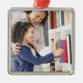 Mother helping daughter choose book on shelf christmas ornament