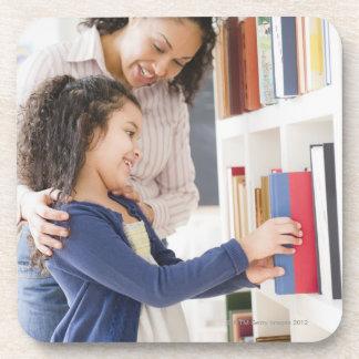 Mother helping daughter choose book on shelf coaster