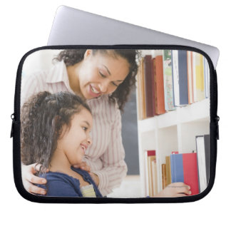 Mother helping daughter choose book on shelf laptop sleeve