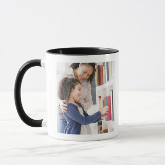 Mother helping daughter choose book on shelf mug
