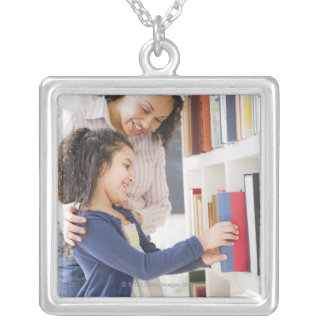 Mother helping daughter choose book on shelf silver plated necklace
