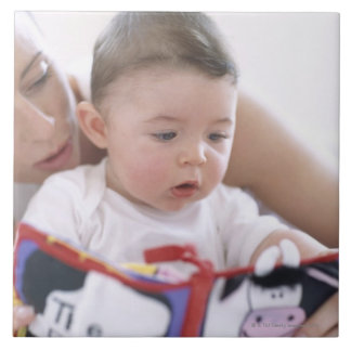 Mother reading to baby boy. Faces of a mother Tile