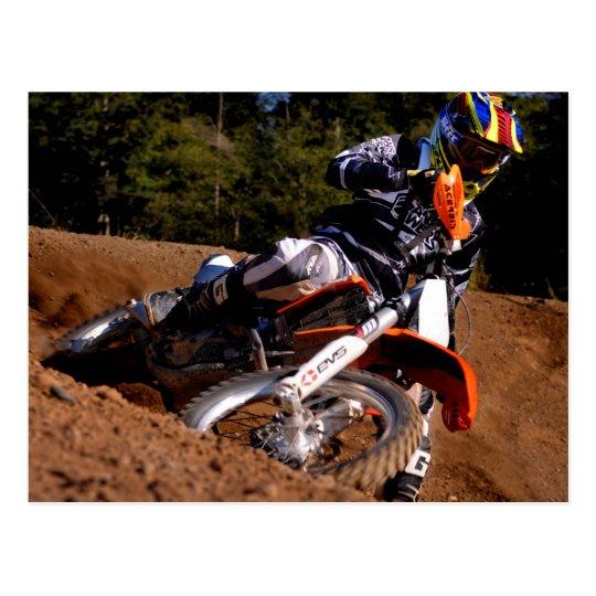 Motocross rider racing through the turn postcard
