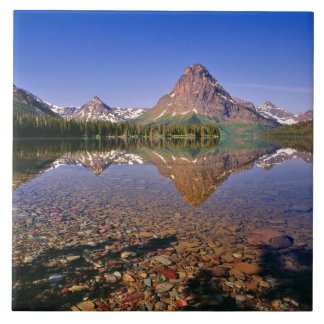 Mountains reflect into calm Two Medicine Lake in Tile