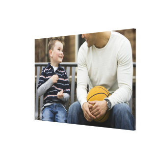 MR Man (age 25) and boy (age 6) sitting on park Canvas Print