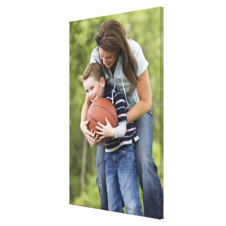 MR mother (age 26) playing basketball with son Canvas Print