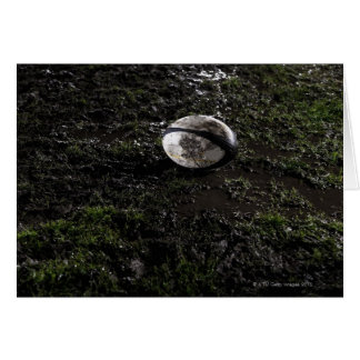 Muddy rugby ball sitting on a chewed up grass card