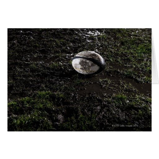 Muddy rugby ball sitting on a chewed up grass cards