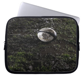 Muddy rugby ball sitting on a chewed up grass laptop sleeve