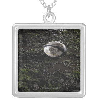 Muddy rugby ball sitting on a chewed up grass silver plated necklace
