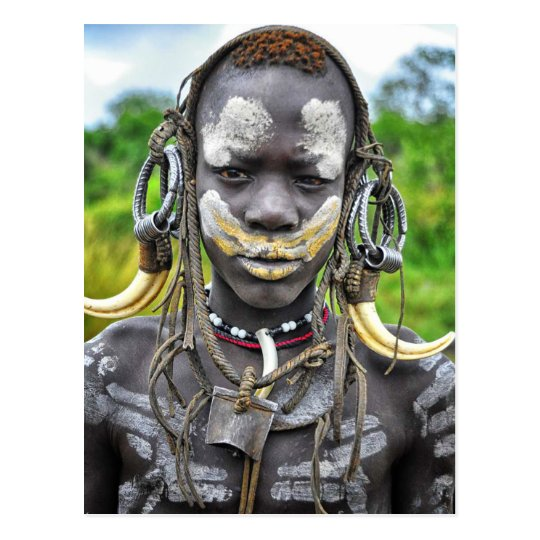 Mursi boy with painted body and tusk headdress postcard