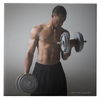 Muscular man lifting dumbbells tile