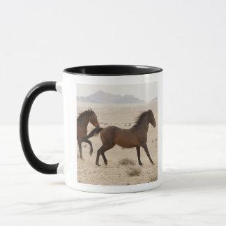 Namibia, Aus. Wild horses running on the Namib Mug