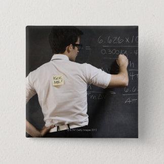 Nerdy man writing on blackboard 15 cm square badge